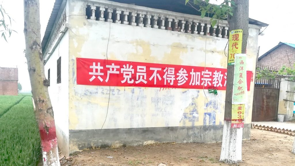 """A banner hanging on the wall, reading """"Communist Party Members Cannot Participate in Religious Activities."""""""