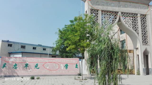 la scritta araba, così come quella cinese e quella inglese, è stata rimossa dal tetto e dall'ingresso della scuola