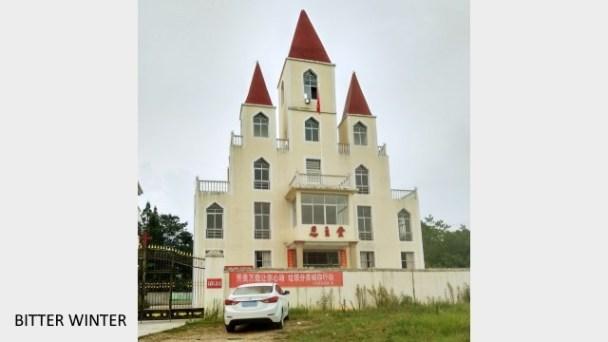 Rimozione della croce dalla chiesa di Enzhu nel villaggio di Menghui, borgo di Kangle, città di Yichun, mentre la bandiera nazionale è issata davanti alla chiesa