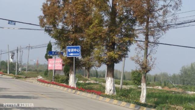 """Sul cartello a lato della strada in un incrocio nel villaggio di Zaoshu è scritto """"Centro di addestramento"""""""