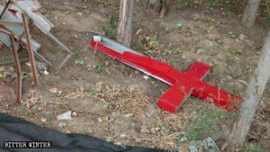 La croce della chiesa del villaggio smantellata e gettata a terra