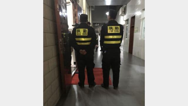 Agenti ausiliari in servizio fanno la guardia all'ingresso della chiesa