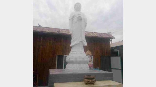 Una tatua buddista in marmo bianco in un tempio nella città di Shenyang prima della rimozione