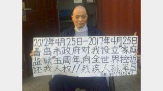 """25 aprile 2017. Sun Jichang, a casa, mostra un cartello: """"Restituitemi i diritti umani"""""""