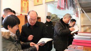 """Il 16 gennaio alcuni funzionari della sezione dell'Ufficio per gli affari etnici e religiosi e di alcuni altri dipartimenti governativi della città di Zhangjiagang esaminano i libri religiosi """"illegali"""" trovati in una chiesa"""