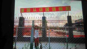 Muro perimetrale dell'asilo munito di filo spinato. Il cartello dice: «L'amore per il tuo Paese inizia parlando in cinese mandarino»
