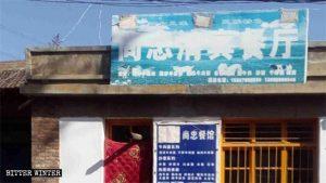 Tre nuovi segni fatti con vernice, nastro adesivo e altro appaiono sull'insegna di un ristorante etnico hui nella municipalità di Taipingdian della città di Baiyi, nella provincia del Gansu