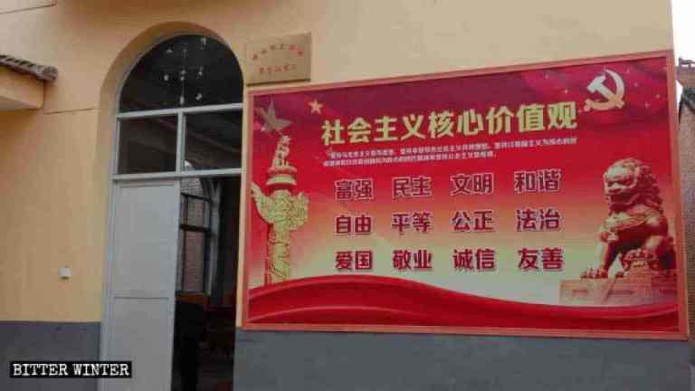 """Il cartello con la scritta """"Camera di consiglio della fattoria"""" e un grande manifesto propagandistico sui """"valori centrali del socialismo"""" affissi sul muro esterno"""