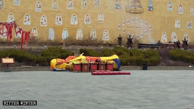 Dopo essere stata smantellata, la statua di Guanyin che stilla acqua è stata posta su un lato e coperta con un telo