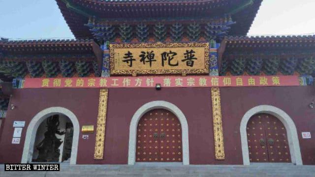 Uno slogan di propaganda del PCC assolutamente ironico recita: «Implementa la politica di libertà delle credenze religiose»: è appeso davanti al tempio Putuo...