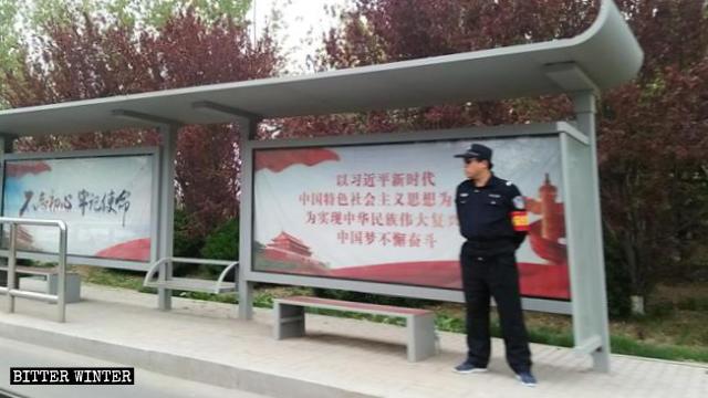 Un agente di sicurezza a una fermata dell'autobus a Qindao