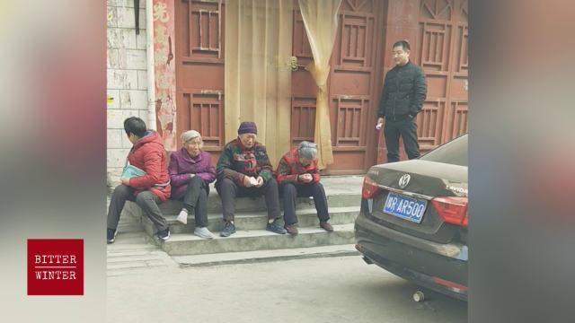 Anziano fedele in lacrime prega davanti alla porta chiusa della chiesa