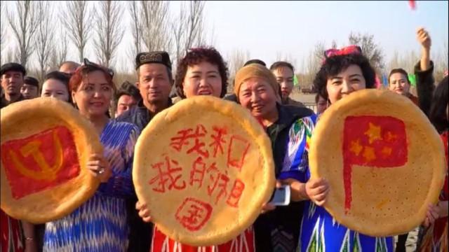 """Da sinistra a destra pani nan uiguri """"decorati"""" con la falce e martello del PCC, lo slogan «io e il mio Paese» e la bandiera cinese nel corso delle celebrazioni di primavera svoltesi a Turpan, nello Xinjiang"""