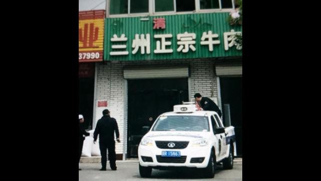 Poliziotti mentre smantellano i caratteri arabi che significano halal