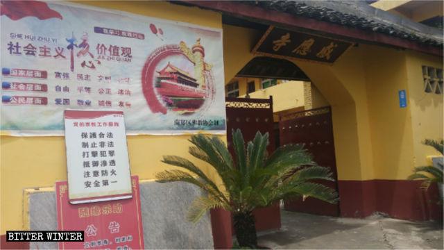 Un poster che riporta i valori centrali del socialismo è esposto all'ingresso di un tempio nella città di Hanzhong nello Shaanxi