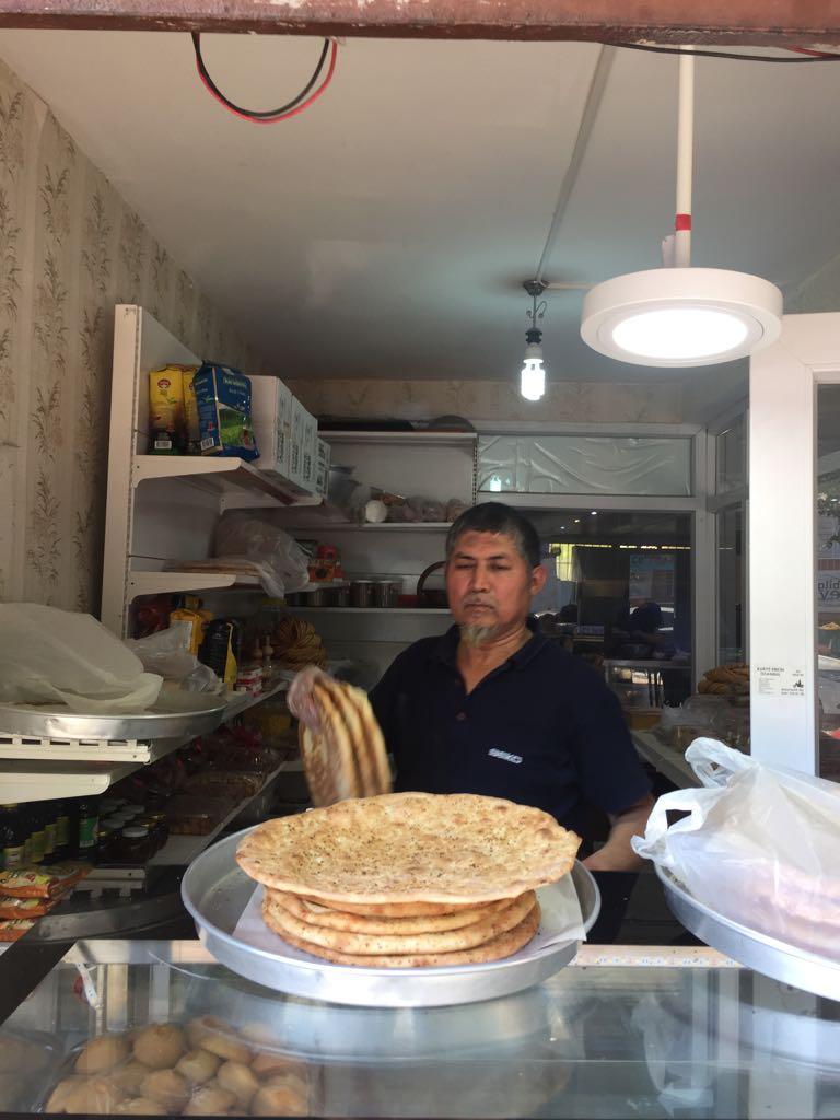 """Un panettiere di Kashgar mostra con orgoglio il pane """"naan"""" appena tolto dal forno Tandoor"""