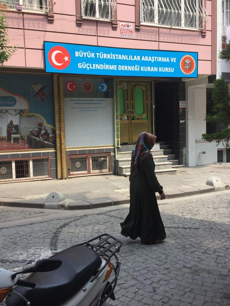 Una donna uigura passa davanti a una piccola madrassa (scuola di formazione islamica) per l'istruzione coranica nel distretto di Ziyghur a Zeytinburnu