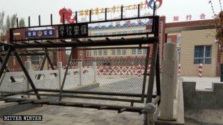 Questa scuola elementare nella contea di Lop nello Xinjiang accoglie i bambini i cui genitori sono stati rinchiusi nei campi per la trasformazione attraverso l'educazione e il cancello è rigorosamente sorvegliato