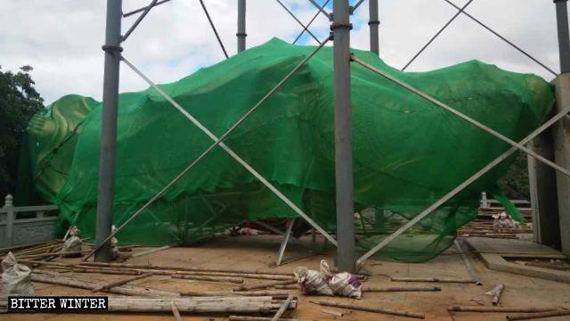 La statua della Guanyin è stata posata a terra e coperta con una rete verde