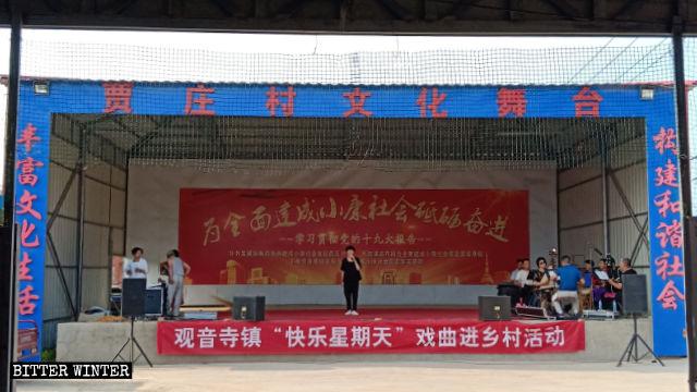 Uno spettacolo è in corso nel Teatro culturale del villaggio di Jiazhuang e sul palco è appeso uno striscione con scritto «Domenica felice»