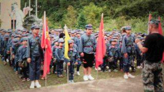 Gli studenti indossano l'uniforme dell'Esercito Popolare di Liberazione e portano zaini con stampati il ritratto del presidente Mao e lo slogan «Servire il popolo»
