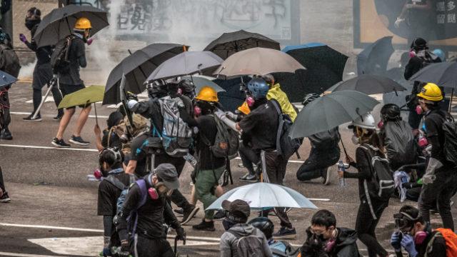 I manifestanti e i reporter di Hong Kong hanno bisogno di maschere e ombrelli per resistere agli attacchi con i gas lacrimogeni della polizia