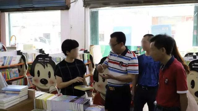 Funzionari governativi ispezionano le pubblicazioni in una libreria nella provincia del Guangdong