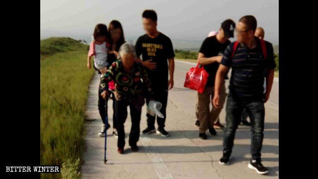 Una donna anziana, con i capelli bianchi, ha dovuto usare un bastone per raggiungere il luogo del pellegrinaggio, in cima al monte