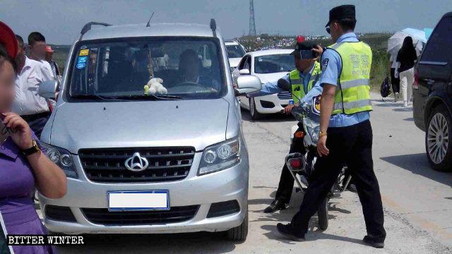 La polizia ferma i veicoli lungo la strada verso il luogo del pellegrinaggio sul monte Mozi