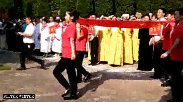 Le squadre delle varie regioni eseguono la cerimonia dell'alzabandiera di fronte alla chiesa prima delle gare