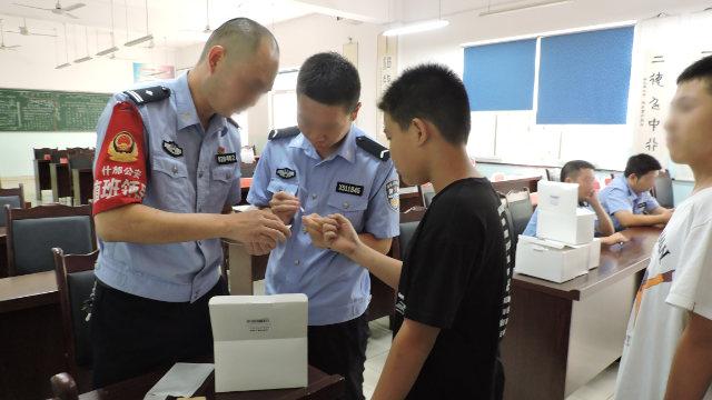 Agenti dell'Ufficio per la sicurezza pubblica della città di Shifang nel Sichuan raccolgono i campioni del DNA degli studenti delle scuole medie