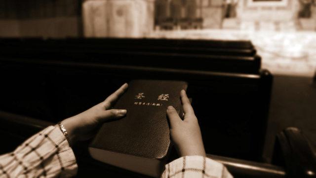 Una fedele con una Bibbia, libro sacro che la polizia confisca sempre durante le perquisizioni nelle Chiese domestiche