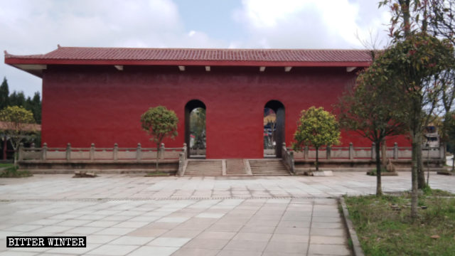"""Cinque grandi statue che sorgevano all'aperto sono state """"confinate"""" in un edificio dipinto di colore rosso."""