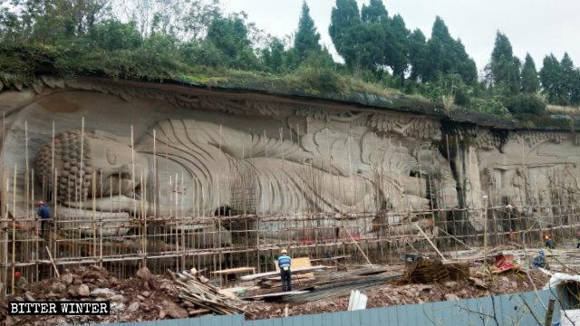 Gli operai al lavoro per coprire la statua del Buddha disteso nella zona panoramica del monte Lingyun