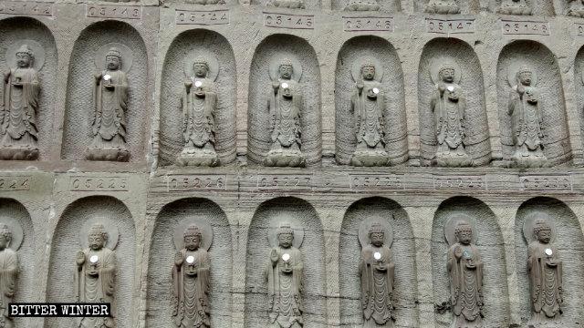 Primo piano delle statuette del Buddha intagliate nelle pareti