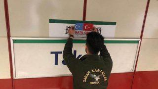 Un giovane turco, simpatizzante per la causa uigura, copre l'indicazione in mandarino della fermata di piazza Taksim della linea tramviaria con le bandiere del Turkestan orientale e della Turchia, insieme alla scritta «katil çin», ovvero «assassino cinese»