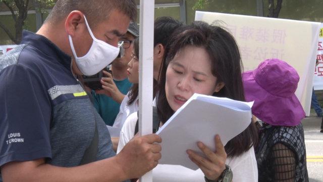 Durante la dimostrazione O Myung-ok controlla un testo scritto a mano con un parente di un fedele