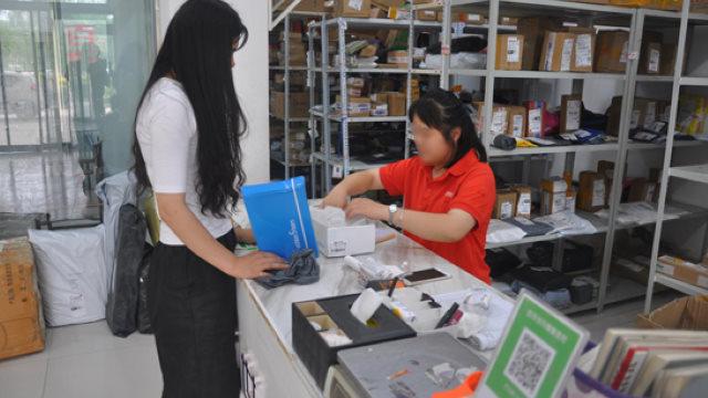 I dipendenti di una società di consegna aprono i pacchi per controllarli