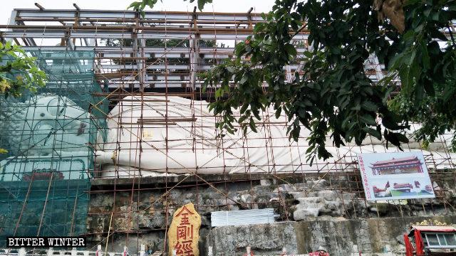 La grande scultura del Buddha disteso viene coperta