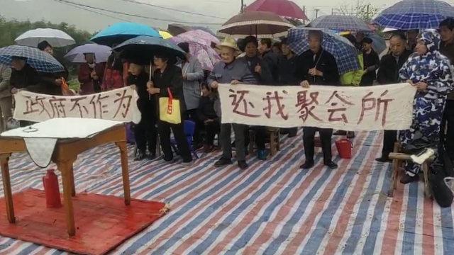 I fedeli radunati sulle rovine della propria chiesa distrutta reggono due striscioni con messaggi rivolti allo Stato