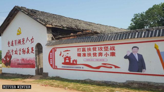 Cartelloni di propaganda che promuovono la campagna per la riduzione della povertà affissi sui muri delle case nelle zone rurali