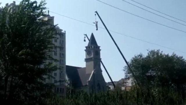 Una gru rimuove la statua di Gesù dal campanile della chiesa cattolica nel villaggio di Linjiazhuang