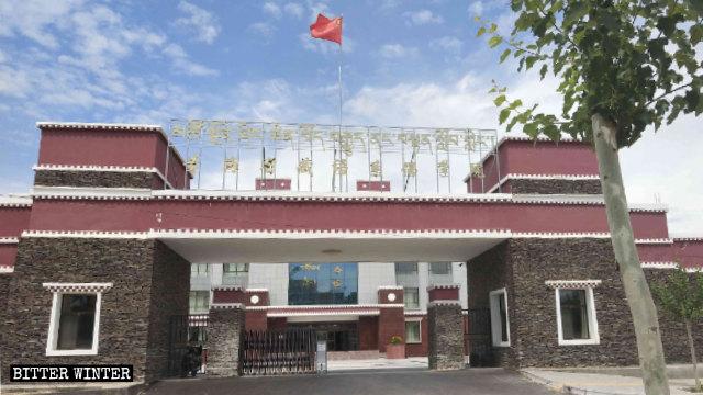 La bandiera cinese sventola sul cancello del Tibetan Buddhist College di Qinghai