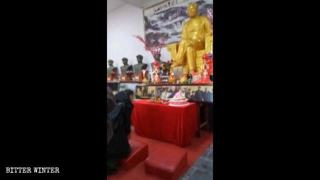 Persone inginocchiate davanti alla statua di Mao Zedong, a Shangrao, il 26 dicembre