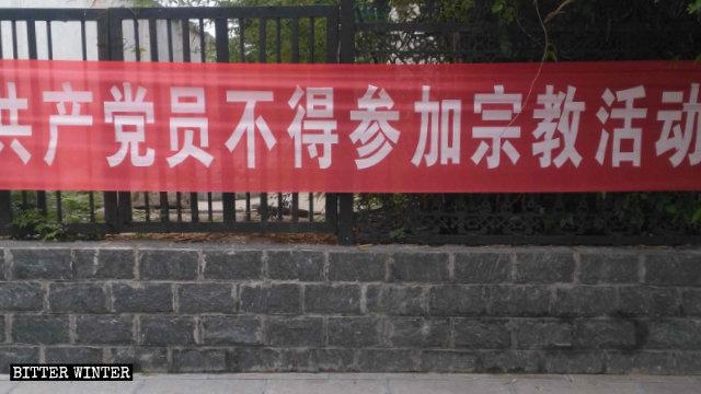 Uno striscione esposto in una strada di Shangbali, un borgo nella giurisdizione della città di Huixian nella provincia dell'Henan, proibisce ai membri del Partito di partecipare ad attività religiose