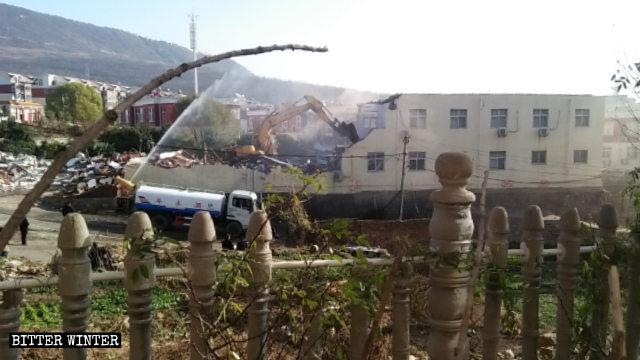 Un escavatore al lavoro per demolire la chiesa di Sigou