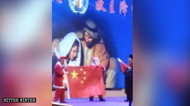 Un attore che recita la parte di Babbo Natale mostra la bandiera cinese durante la rappresentazione