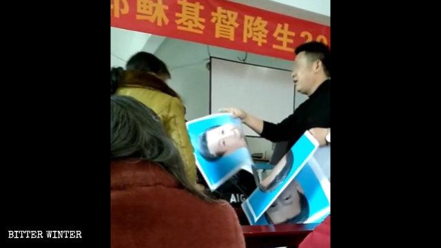 Un funzionario dell'amministrazione distribuisce ai fedeli i ritratti di Xi Jinping