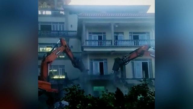 gli escavatori demoliscono lo stabile