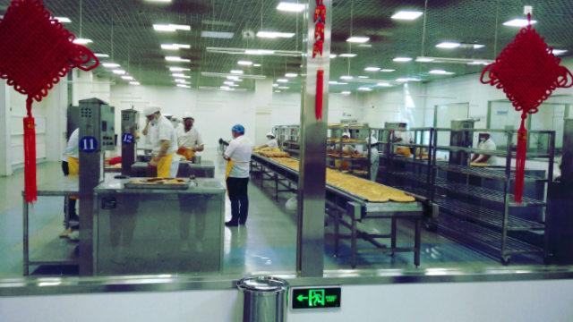 Uiguri intenti a preparare il pane naan